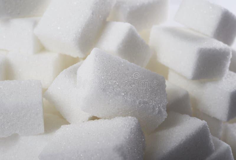 Den isolerade högen av socker skära i tärningar tätt upp sikt i söt näring och bantar begrepp arkivfoton