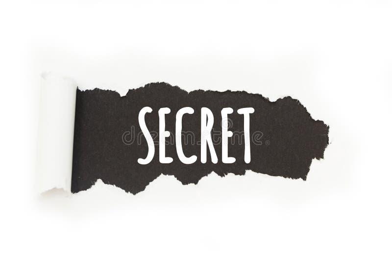 Den isolerade inskriften 'hemlighet 'på en svart bakgrund, papper brister royaltyfri illustrationer
