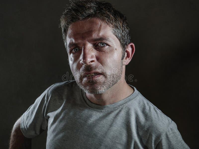 Den isolerade mörka bakgrundsståenden av den unga rubbningen och den utmanande mannen i arrogant och kaxigt poserar att se med fö fotografering för bildbyråer