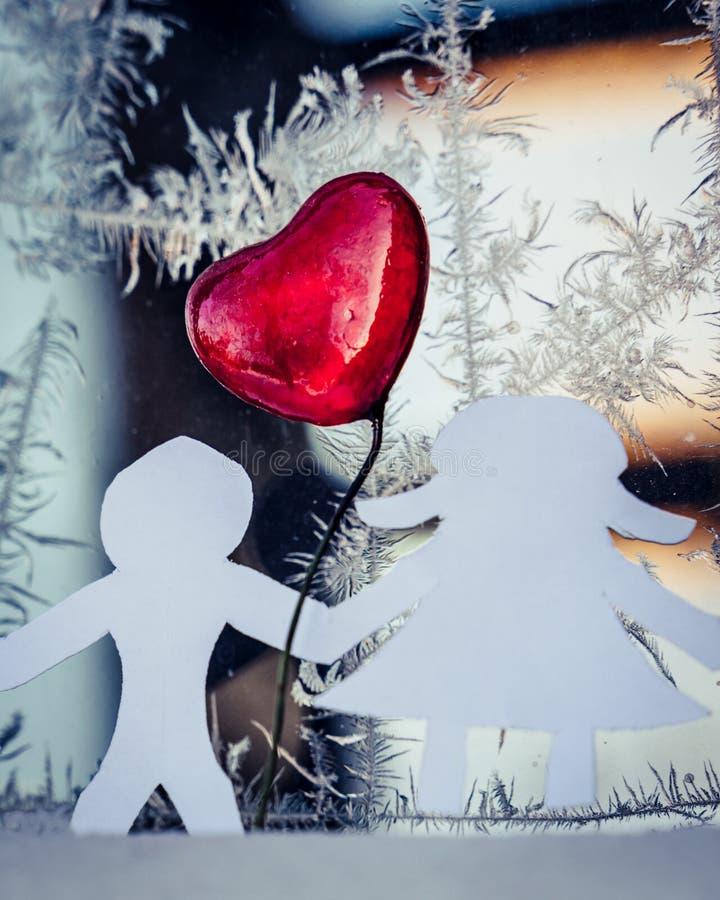 Den isolerade origamin skyler över brister pojken och pappersflickan som dem emellan rymmer händer med en röd hjärta och rimfrost royaltyfria foton