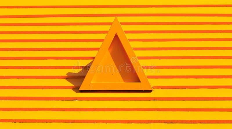 Den isolerade triangelapelsinen målade form på det gula trätaket stock illustrationer