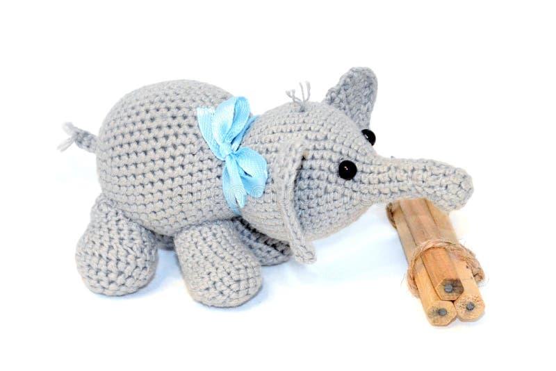 Den isolerade virkade gråa elefanten med en blå pilbåge på halsen står bredvid en grupp av träblyertspennor på en vit bakgrund arkivfoto