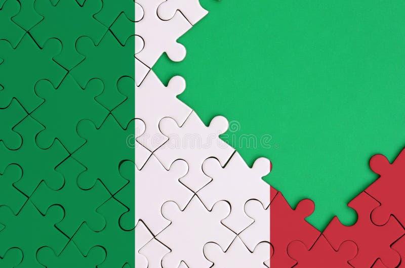 Den Italien flaggan visas på ett avslutat pussel med fritt grönt kopieringsutrymme på rätsidan royaltyfri fotografi