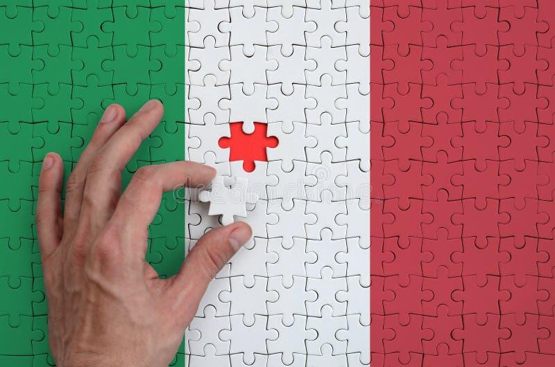 Den Italien flaggan visas på ett pussel, som handen för man` s avslutar för att vika arkivfoton