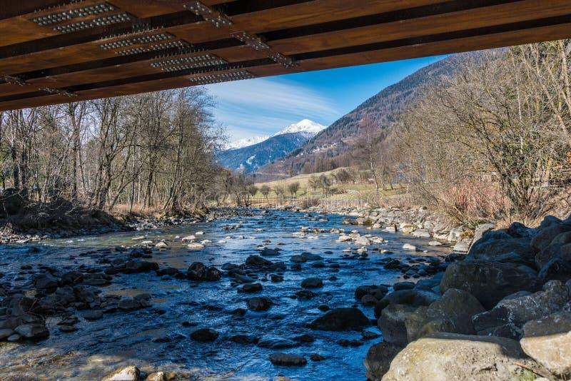 Den italienska bergfloden kallade den Noce floden Sikt under bron Snö täckte berg - Termenago, Val di Sole, Italien, Europa royaltyfri foto