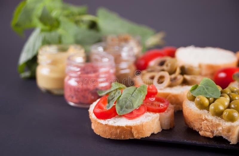 Den italienska bruschettaen i sortiment på plattan, ställde in med den lilla flaskan av senap arkivbilder