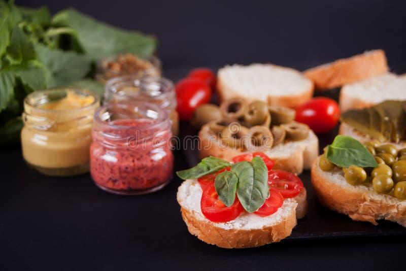 Den italienska bruschettaen i sortiment på plattan, ställde in med den lilla flaskan av senap fotografering för bildbyråer
