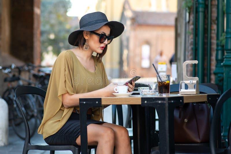 Den italienska kvinnan med hatten och exponeringsglas skriver meddelandet med smartphonen arkivfoto
