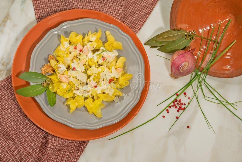 Den italienska maträtten av den handgjorda tortellinien med laxen, kräm och rosa färger pepprar Dekorerat med lagerbladen, löken  arkivfoton