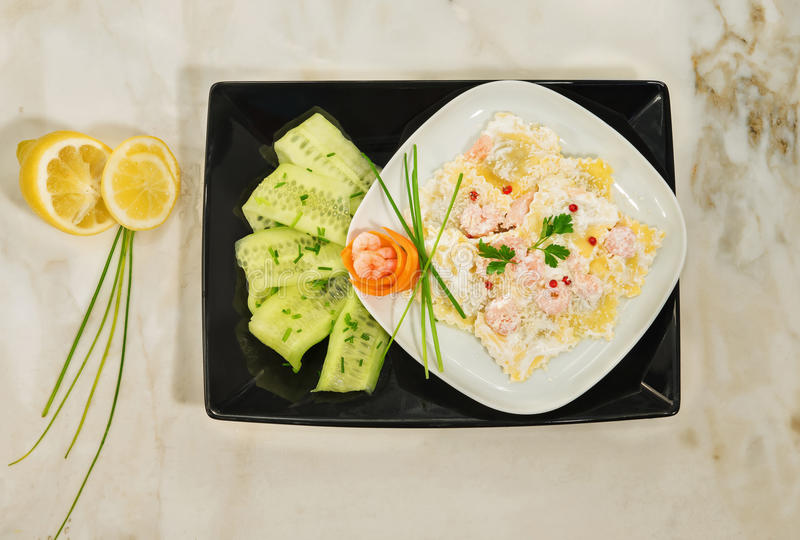 Den italienska maträtten av den hemlagade raviolit med kräm, räka, rosa färg pepprar och aromatiska örter arkivfoton