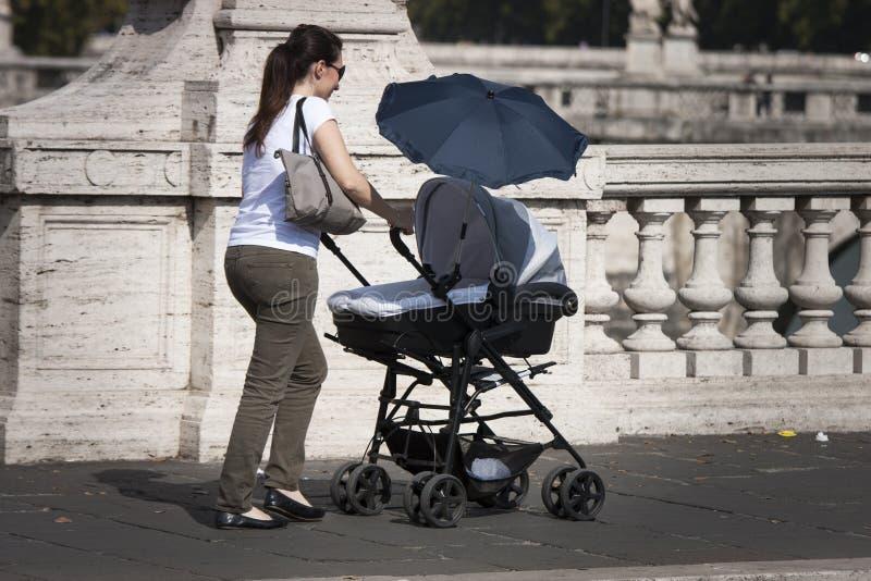 Den italienska modern och behandla som ett barn i en pram arkivfoto