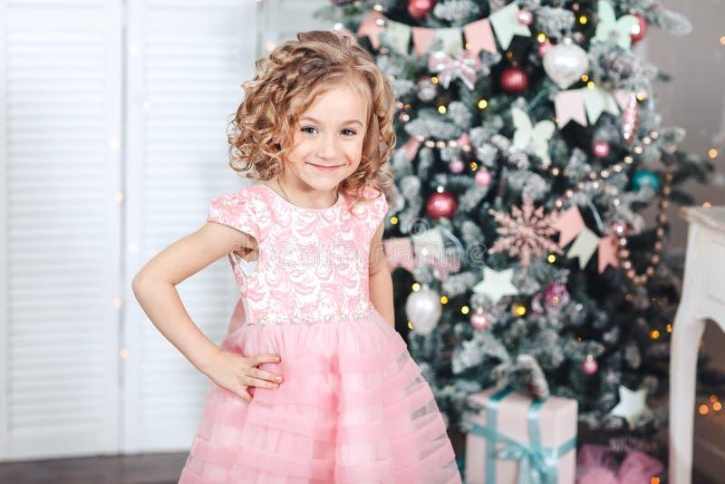 Den Ittle flickan i en högtidlig rosa färgklänning står nära julgranen royaltyfri fotografi