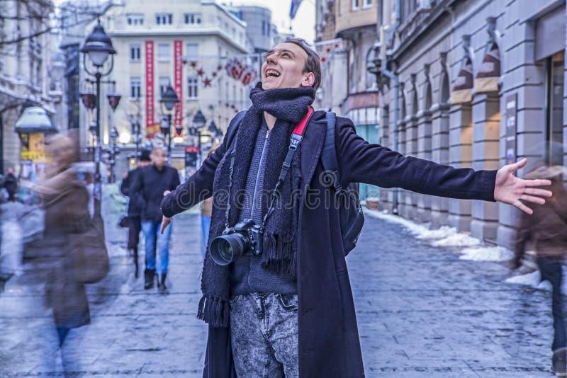 Den jätteglade fotografen som ler med hans armar, fördelade vitt i den huvudsakliga gatan av Belgrade arkivfoton