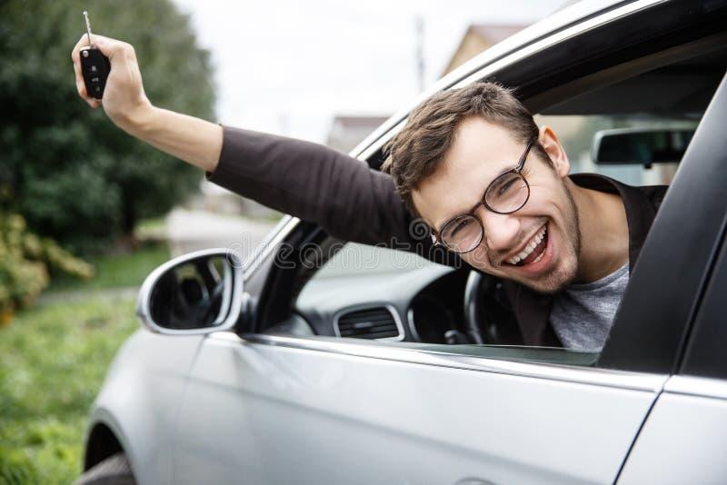 Den jätteglade unga mannen kikar från bilfönstret, medan se kameran Han rymmer tangenterna på hans assistent lotteri royaltyfria foton