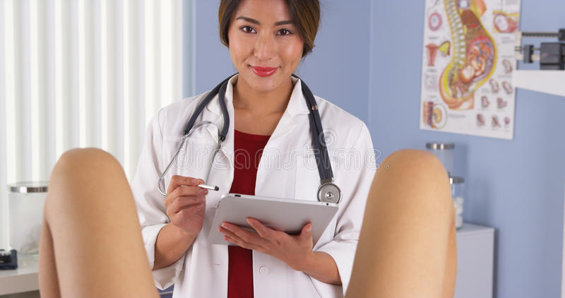 Den japanska gynekologen undersöker patienten i sjukhusexamenrum arkivbilder