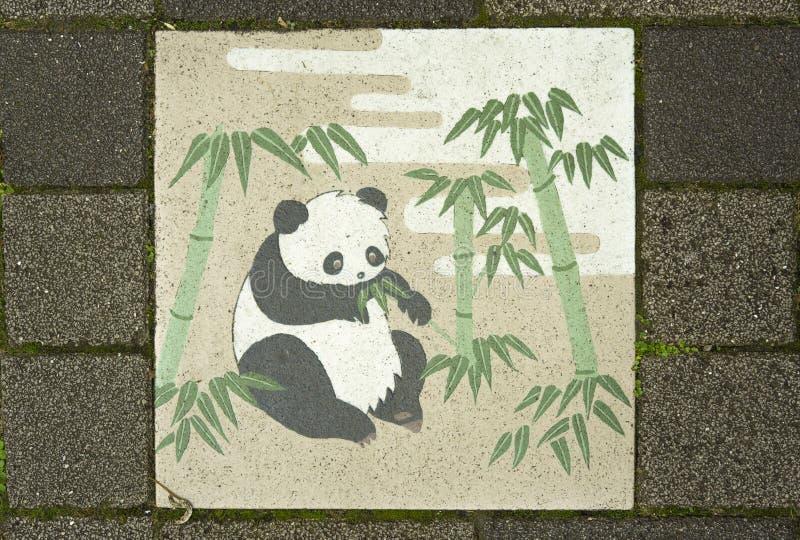 Den japanska keramiska tegelplattan dekorerade med den gulliga pandan som äter bambu le fotografering för bildbyråer
