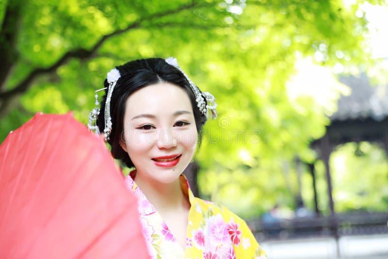Den japanska kvinnan med kimonot i en vår parkerar japanskt le för brud arkivfoto