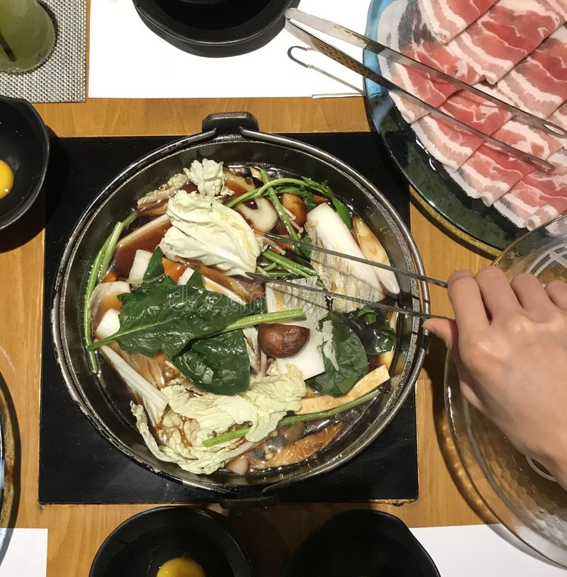 Den japanska nabemonohotpotmaträtten av den tunt skivade kött och grönsaken kokade i vatten som tjänades som med att doppa såser, royaltyfria foton