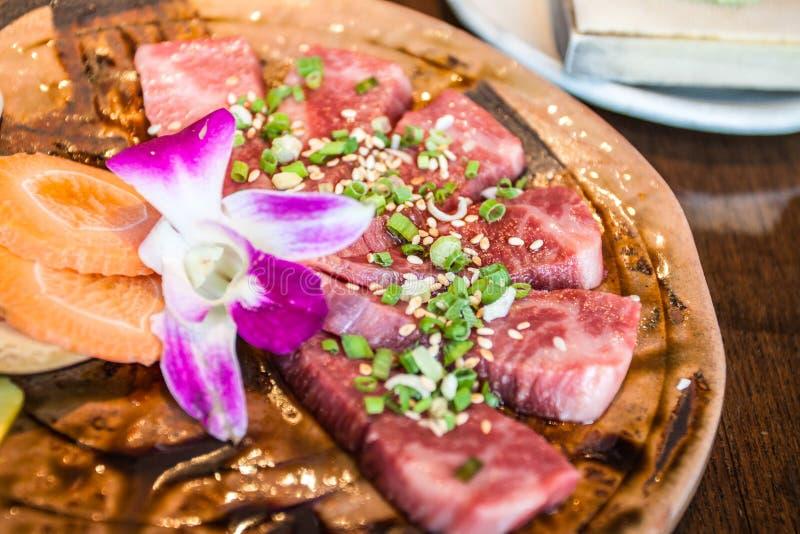Den japanska restaurangen som tjänar som mouthwatering disk, nytt griskött, dekorerade med blommor royaltyfria foton