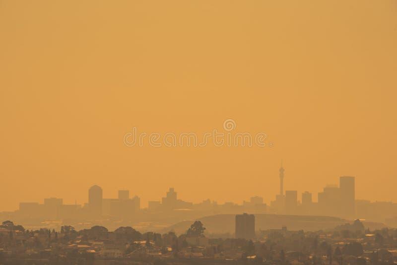 Den Johannesburg horisonten silhouetted mot en guld- himmel arkivfoton