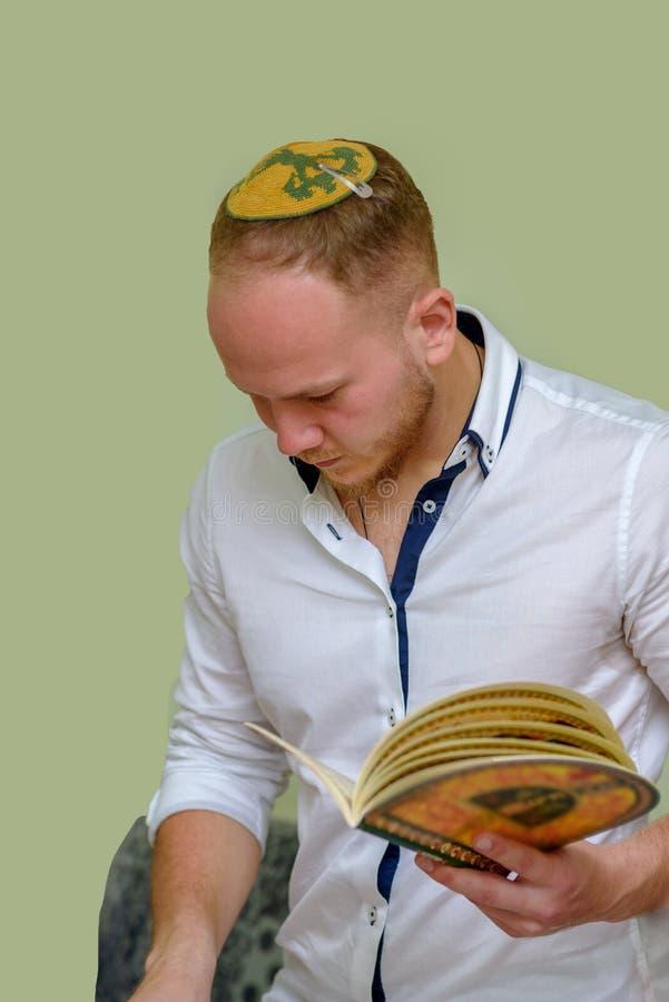 Den judiska mannen läser påskhögtidhaggadahen arkivbilder