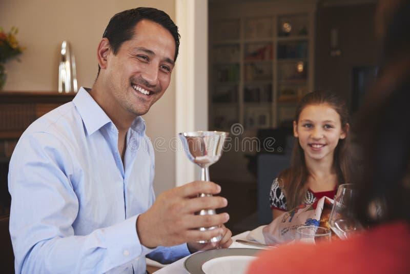 Den judiska mannen som rymmer den kiddish koppen, välsignar familjen på Shabbat royaltyfri bild