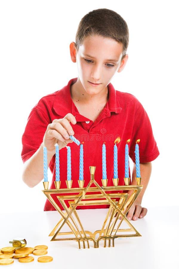 Den judiska pojken tänder menoror royaltyfri fotografi