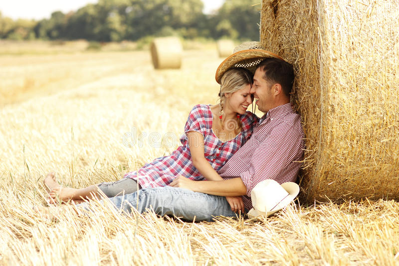 In den jungen Paaren der Liebe auf Heuschobern in den Cowboyhüten lizenzfreies stockbild