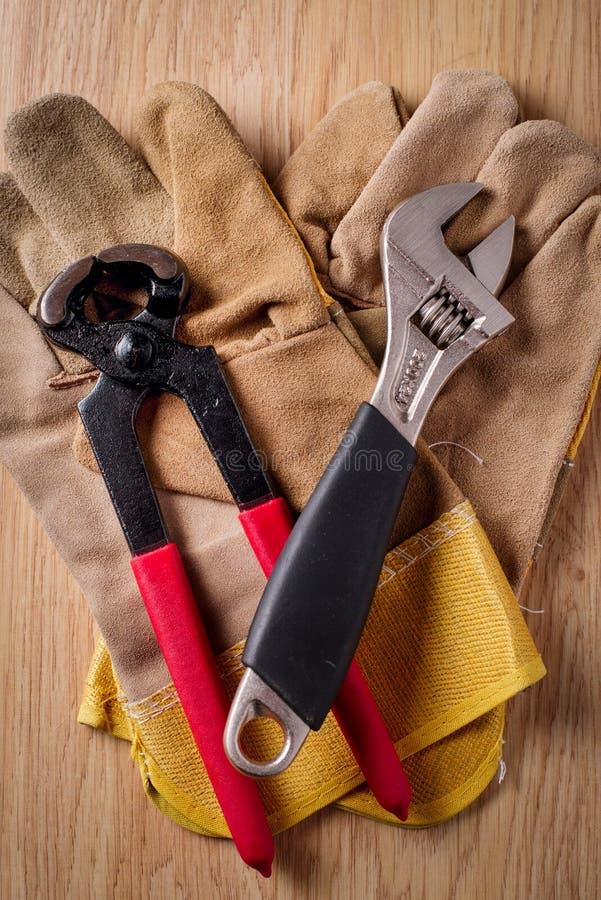 Den justerbara skiftnyckeln och spikar pulleren överst av de skyddande handskarna arkivfoton