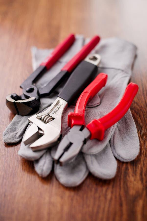 Den justerbara skiftnyckeln, plattång och spikar pulleren överst av de skyddande handskarna arkivfoto