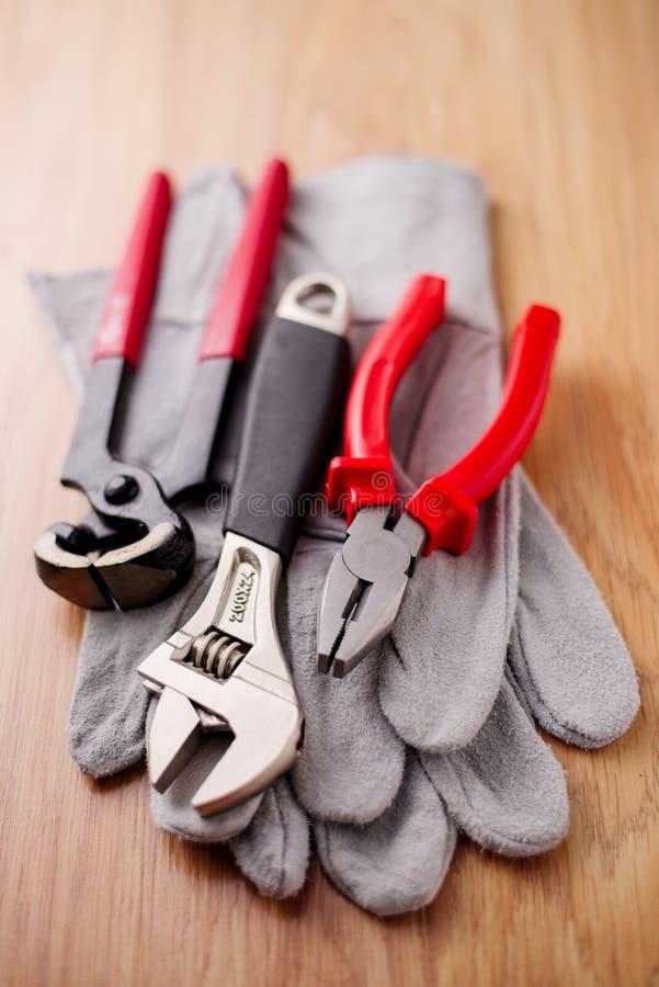 Den justerbara skiftnyckeln, plattång och spikar pulleren överst av de skyddande handskarna royaltyfria bilder