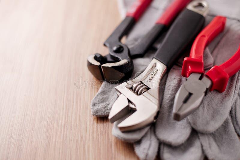 Den justerbara skiftnyckeln, plattång och spikar pulleren överst av de skyddande handskarna royaltyfri fotografi