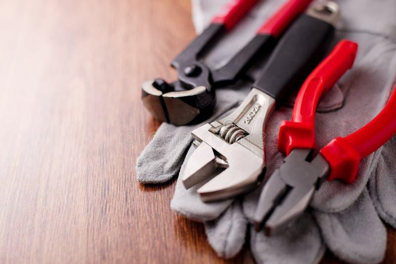 Den justerbara skiftnyckeln, plattång och spikar pulleren överst av de skyddande handskarna royaltyfri foto