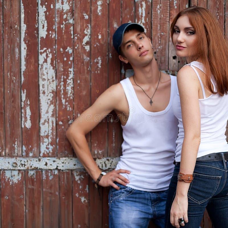 Den känslobetonade ståenden av ett stilfullt kopplar ihop i jeans som tillsammans står arkivbild