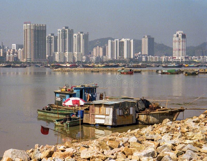 Den kåkfiskebåtar och kojan är på banken av en flod royaltyfri foto