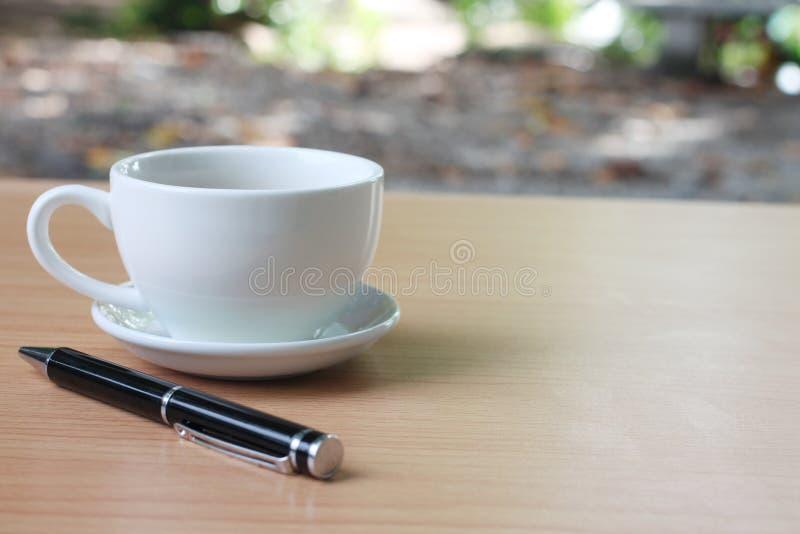 Den kaffekoppen och pennan förläggas på en brun trätabell och har c fotografering för bildbyråer