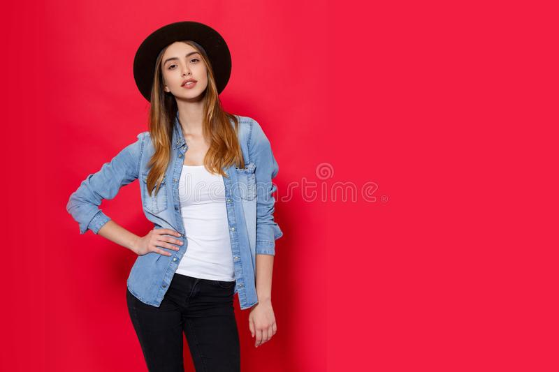 Den kalla flickan i trendig dr?kt poserar med attitudine i studio p? r?d ljus bakgrund placera text royaltyfria foton