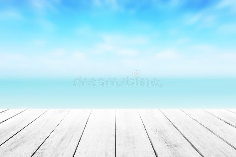 Den kalla havsbakgrunden för suddighet med wood golvförgrund på den tropiska sandiga stranden för horisont; arkivbild