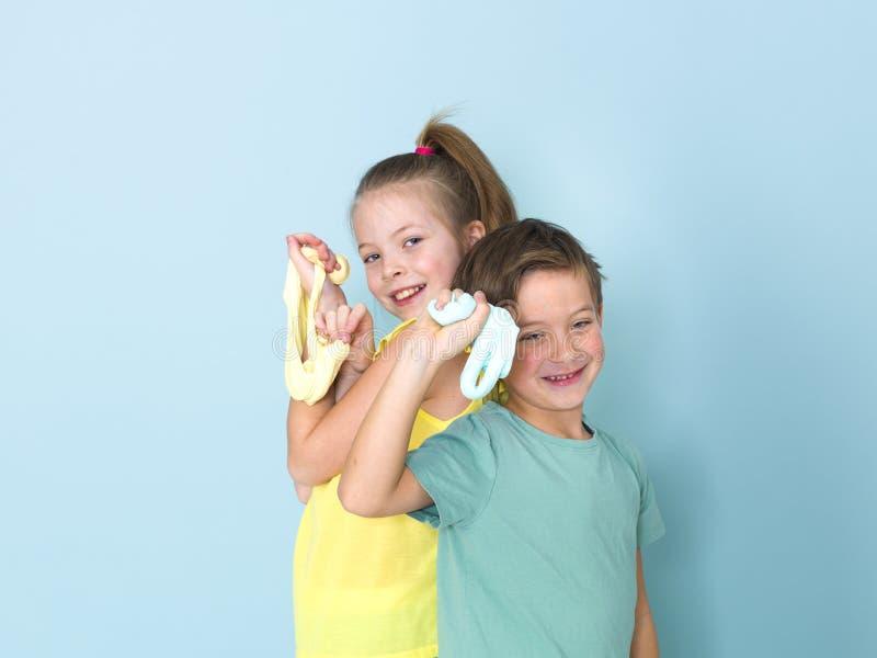 Den kalla nätta pojken och hans äldre syster spelar med hemlagad slam framme av en blå bakgrund och har mycket gyckel royaltyfri fotografi