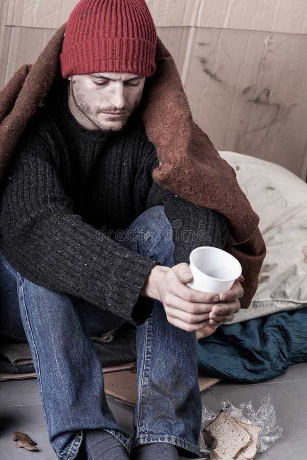 Den kalla och hemlösa mannen tigger för pengar royaltyfri bild