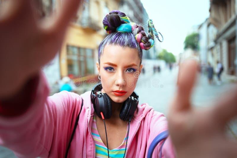 Den kalla skraj unga flickan med hörlurar och galet hår tycker om makt av musik som tar selfie på gatan arkivfoton