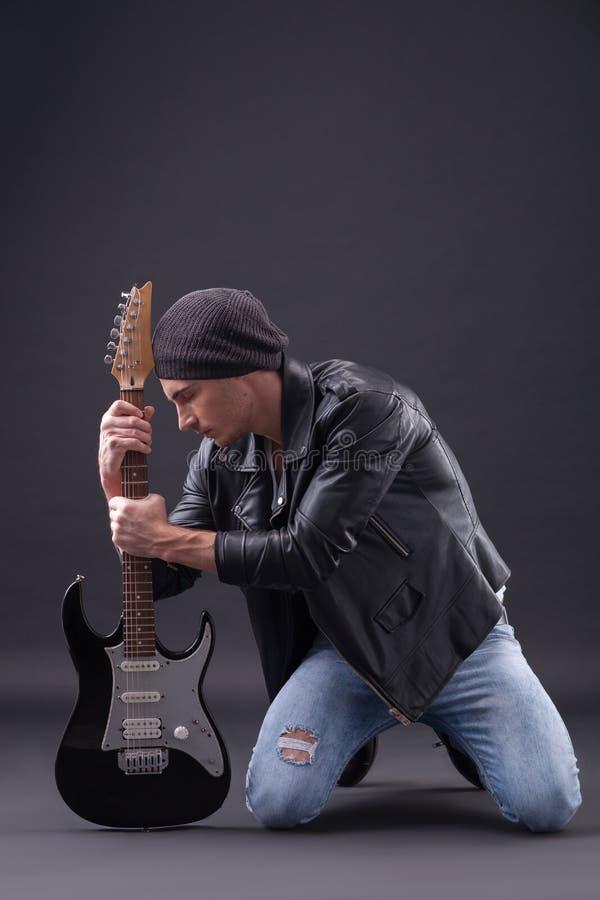 Den kalla unga manliga gitarristen är mycket frustrerad royaltyfria bilder