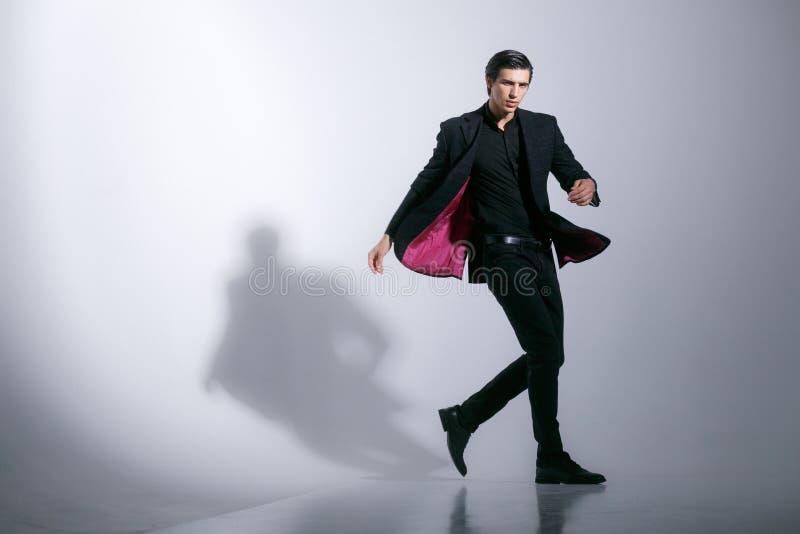 Den kalla unga mannen i stilfull elegant dräkt vänder omkring, poserar säkert i studio, på en vit bakgrund royaltyfri foto
