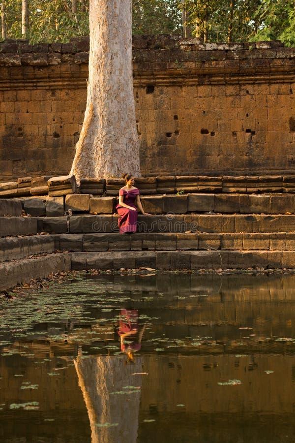 Den kambodjanska flickan i en khmerklänning sitter vid en pöl av vatten i Angkor Thom arkivbilder