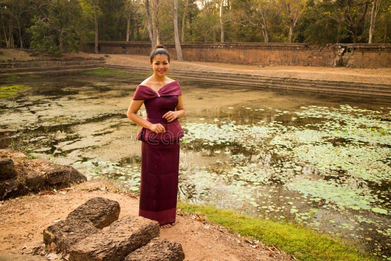 Den kambodjanska flickan i en khmerklänning står vid en pöl av vatten i Angkor Thom royaltyfri fotografi