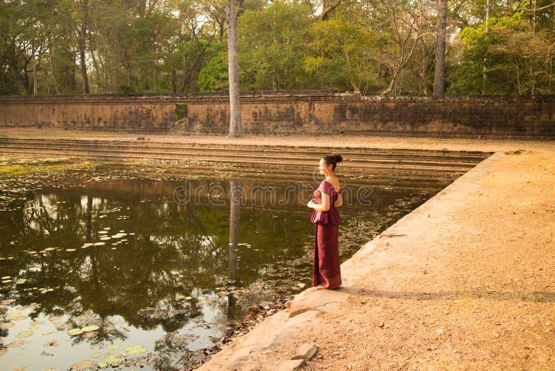 Den kambodjanska flickan i en khmerklänning står vid en pöl av vatten i Angkor Thom arkivfoton