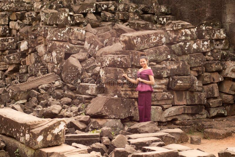 Den kambodjanska flickan i en khmerklänninganseende fördärvar förbi av den Bayon templet i den Angkor staden arkivfoto