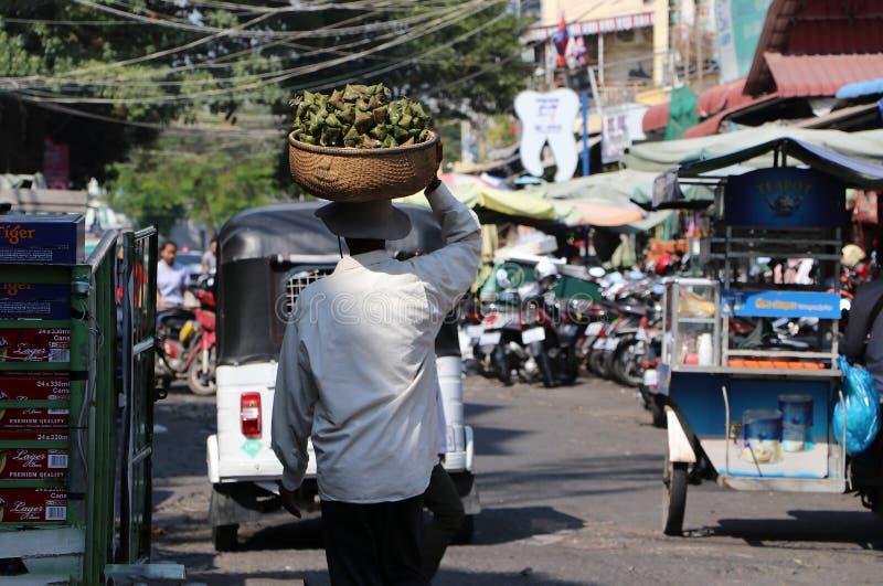 Den kambodjanska manliga gatuförsäljaren satte korgen av triangelpinneris i bambusidorna på hans huvud och att gå i det nytt arkivbild