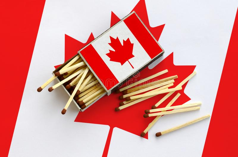 Den Kanada flaggan visas på en öppen tändsticksask, som flera matcher faller från och lögner på en stor flagga arkivbild
