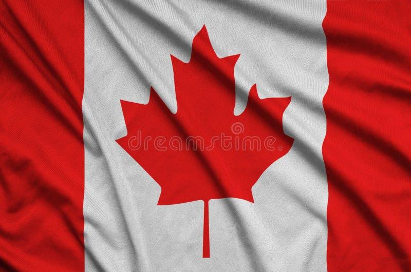 Den Kanada flaggan visas på ett sporttorkduketyg med många veck Baner för sportlag royaltyfria foton
